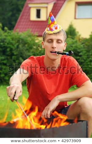 young man with calumet near brazier on picnic, happy birthday pa Stock photo © Paha_L