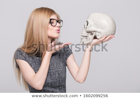 Woman holding and kissing skull in the dark Stock photo © deandrobot