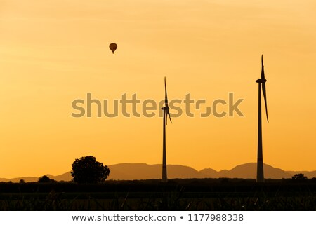Wind generators and Air Baloon in sunrise Stock photo © 5xinc