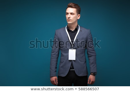 Handsome serious businessman in grey jacket, costly watch and black shirt, black background Stock photo © Traimak
