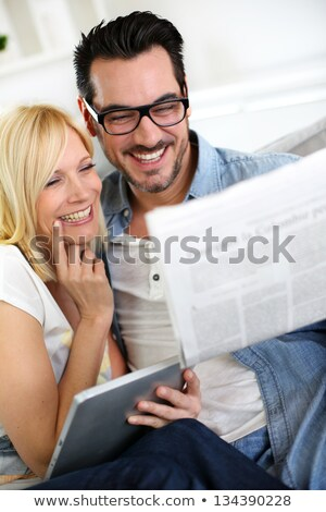 two women reading newspaper laughing stock photo © is2