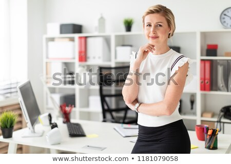 A young girl stands near a table in the office and straightens her glasses with her hand. Stock photo © Traimak
