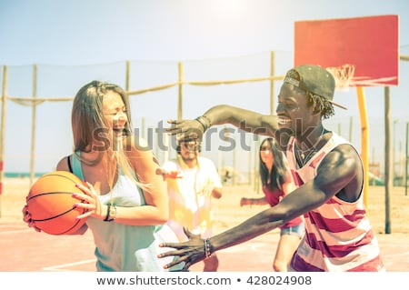 Stock photo: Multiracial couple playing basketball on outdoor court