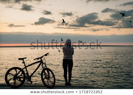 Image of caucasian woman standing with bicycle on boardwalk, dur Stock photo © deandrobot
