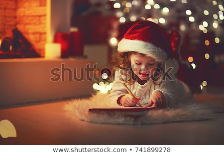little girl writing christmas wish list at home stock photo © dolgachov