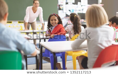 Rear view of a Mixed-race ethnicity schoolgirl siiting on a blue chair looking at the camera in a cl Stock photo © wavebreak_media