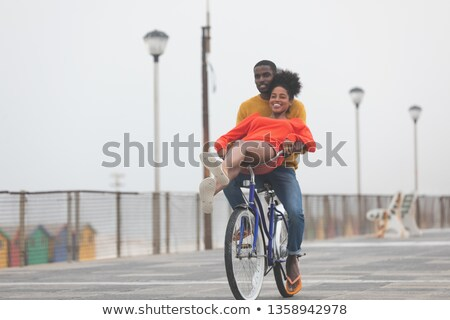 Front view of cute happy Multi-ethnic couple riding bicycle at promenade on a sunny day Stock photo © wavebreak_media