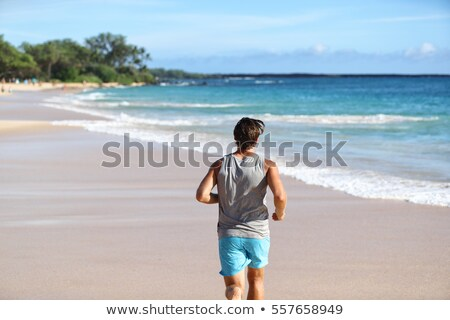 Man athlete running away from behind on beach at sunset. Male runner doing cardio exercise workout o Stock photo © Maridav