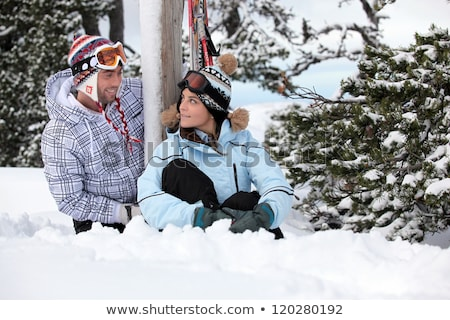 Playful young couple stood by their snowy chalet Stock photo © photography33