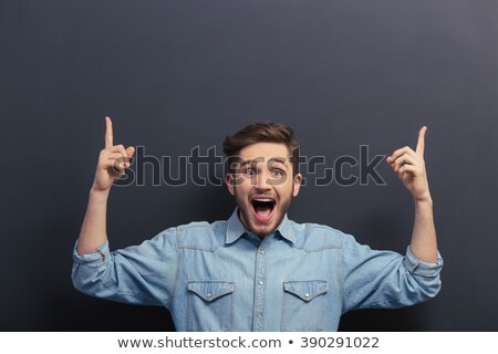 Stock photo: man pointing to an empty chalkboard