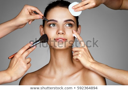 smiling young woman with makeup brushes near her face stock photo © vlad_star