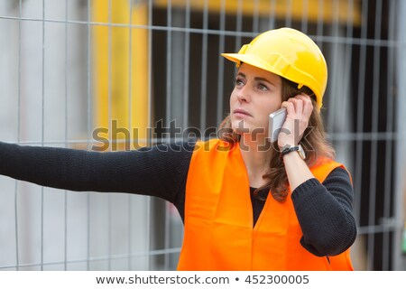 female engineer talking on mobile phone in construction site stock photo © diego_cervo