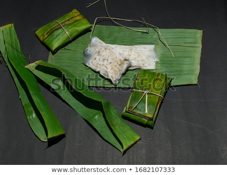 tempeh wrapped in leaf, dark background. Stock photo © szefei