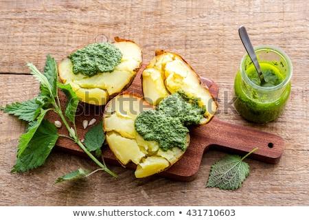 Stock photo: Baked potatoes with pesto sauce close up