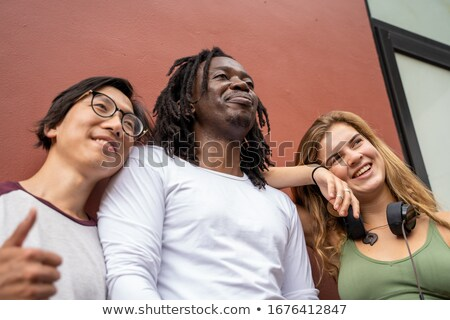 Contemporary young woman with dreadlocks listening to music in headphones Stock photo © pressmaster