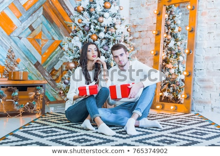 Stock photo: young happy couple near a christmas tree at home holding gift an