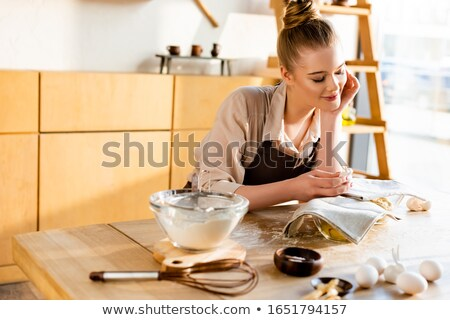 Young woman covered in flour whisking eggs in a bowl Stock photo © serendipitymemories