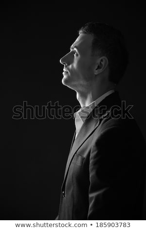 Black and white photo of a pensive man looking up Stock photo © deandrobot