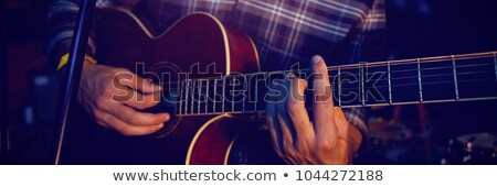 Mid section of male guitarist holding guitar Stock photo © wavebreak_media