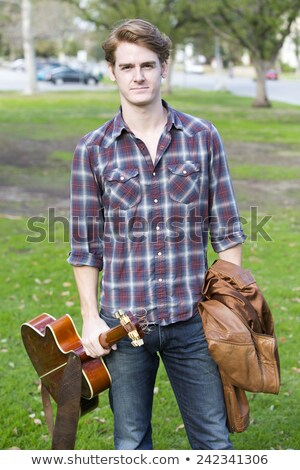 Young man standing in park with guitar Stock photo © manaemedia