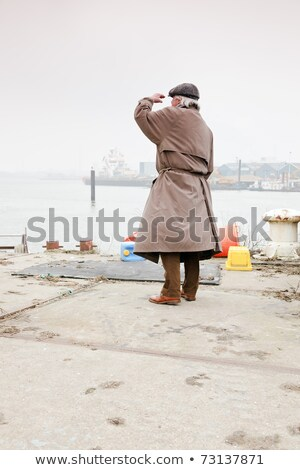 man in raincoat looking on a lake Stock photo © IS2