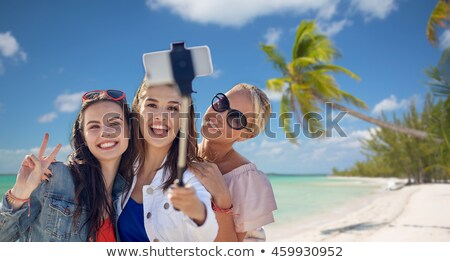 friends taking selfie by monopod over beach Stock photo © dolgachov