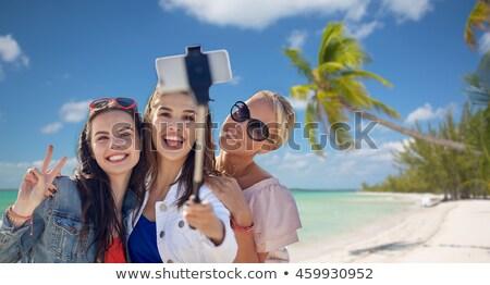 friends taking selfie by monopod over beach stock photo © dolgachov