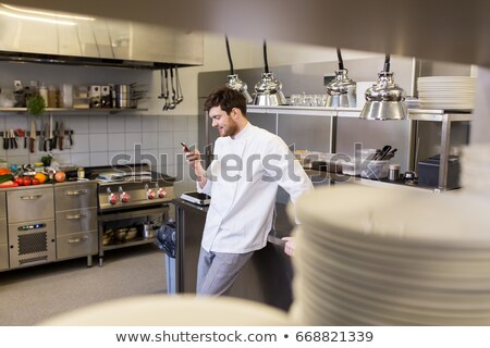 chef cook with smartphone at restaurant kitchen Stock photo © dolgachov