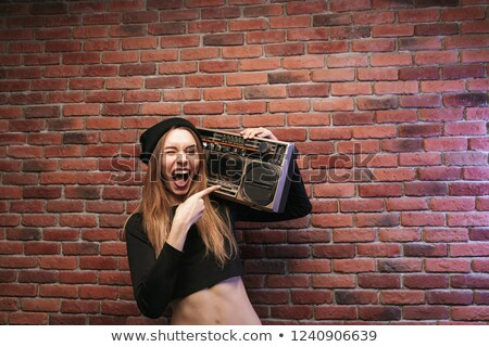 Image of beautiful hip hop woman 20s, standing against brick wal Stock photo © deandrobot