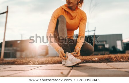 close up of young woman tying shoe laces stock photo © boggy