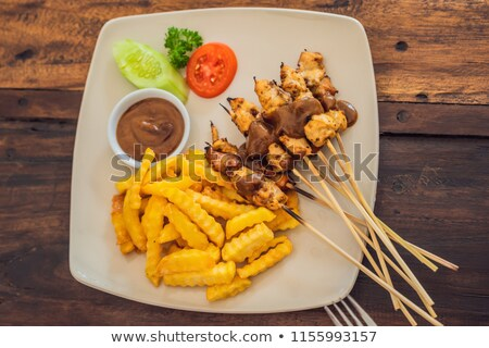 Chicken satay served with peanut sauce and french fries Bali, Lifestyle Stock photo © galitskaya