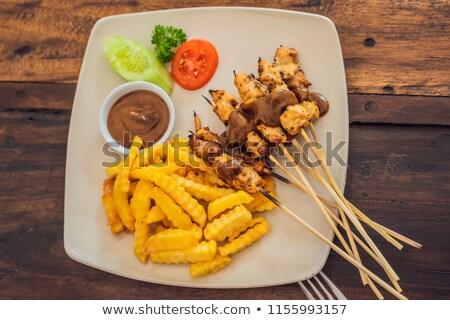 chicken satay served with peanut sauce and french fries bali lifestyle stock photo © galitskaya