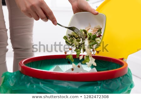 Woman Throwing Food In Trash Bin Stock photo © AndreyPopov