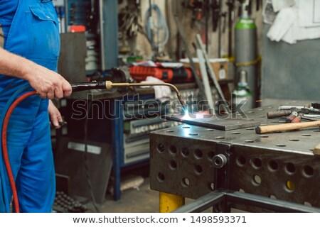 Metalworker heating up piece of metal with burner Stock photo © Kzenon