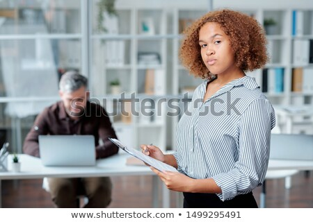 Serious young intercultural secretary with pen and clipboard reading document Stock photo © pressmaster