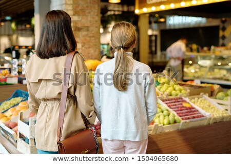 Rear view of young woman and her daughter standing by display with fresh fruits Stock photo © pressmaster