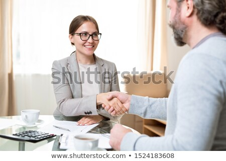 Cheerful agent with toothy smile looking at client while both handshaking Stock photo © pressmaster