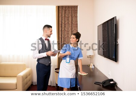 Young chamber maid and porter interacting in one of hotel rooms at work Stock photo © pressmaster