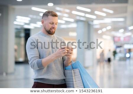Fiatalember okostelefon néz promo képernyő online Stock fotó © pressmaster