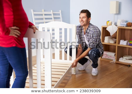 family couple assembling baby bed at home Stock photo © dolgachov