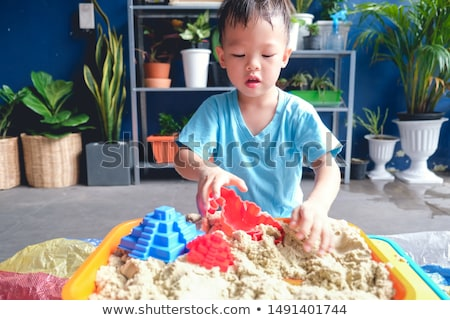 Toddler boy playing with sand on the beach development of fine motor skills Stock photo © galitskaya