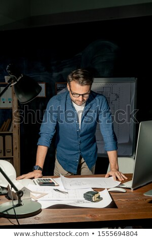 Mature engineer looking at sketch on paper during overtime work at night Stock photo © pressmaster