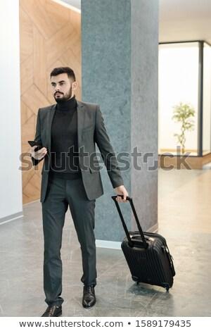 молодые бизнесмен мобильного телефона чемодан багаж Сток-фото © pressmaster