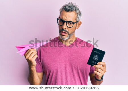 Surprised grey-haired man holding passport with tickets. Stock photo © deandrobot