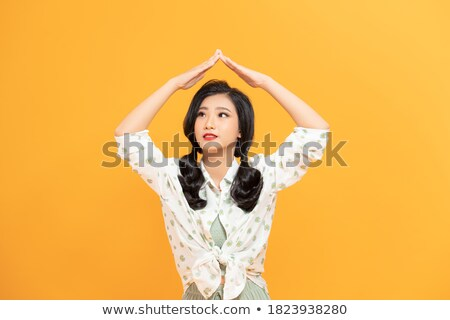 Photo of nice pleased woman making roof gesture and smiling Stock photo © deandrobot