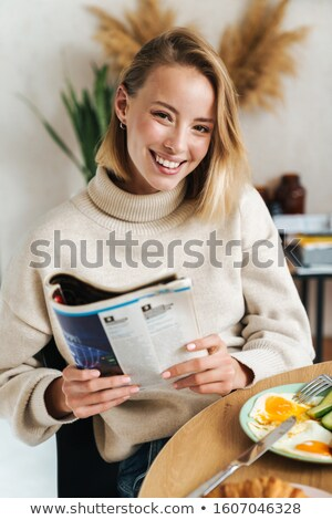 Foto alegre mulher loira leitura revista café da manhã Foto stock © deandrobot