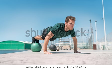 Man doing pushups balancing on medicine ball Stock photo © Maridav