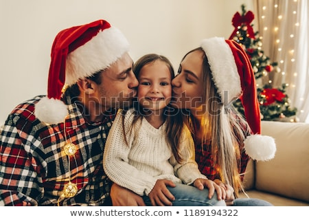 Little girl with her mother sitting together near christmas tree stock photo © HASLOO