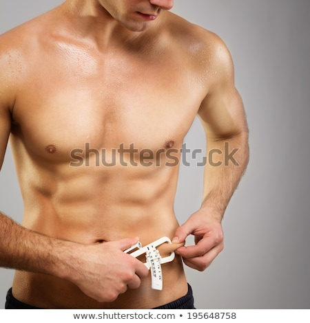 Muscular man measures level of fat on his body Stock photo © dash