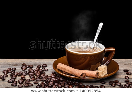 Foto d'archivio: A Cup Of Coffee And Cinnamon Coffee Beans Around It